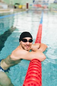 Hombre de alto ángulo con gafas de natación y gorra