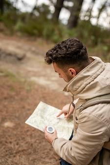Hombre de alto ángulo con mapa y brújula