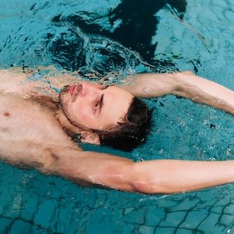 Hombre de alto ángulo nadando en la espalda