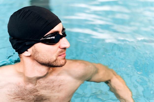 Hombre de alto ángulo en la piscina mirando a otro lado