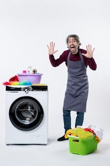 Hombre de ama de llaves vista frontal levantando las manos de pie cerca de la cesta de lavandería lavadora sobre fondo blanco