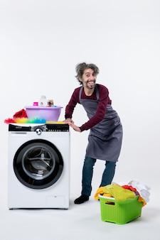 Hombre de ama de llaves vista frontal poniendo las manos en la cesta de lavandería lavadora en el piso