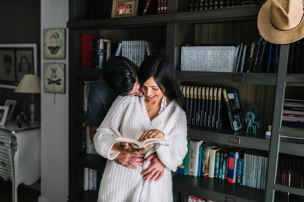 Hombre amando a su novia sosteniendo un libro abierto