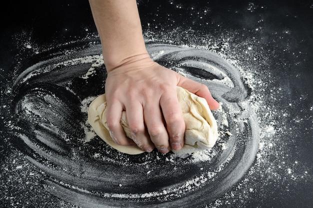 El hombre amasa la masa en una mesa negra espolvoreada con harina.