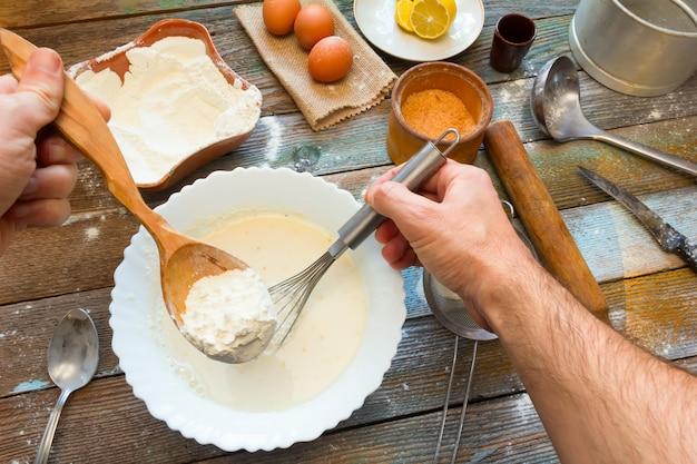 El hombre amasó la masa con un batidor. harina de trigo, rebozado, huevos, un limón y utensilios de cocina.