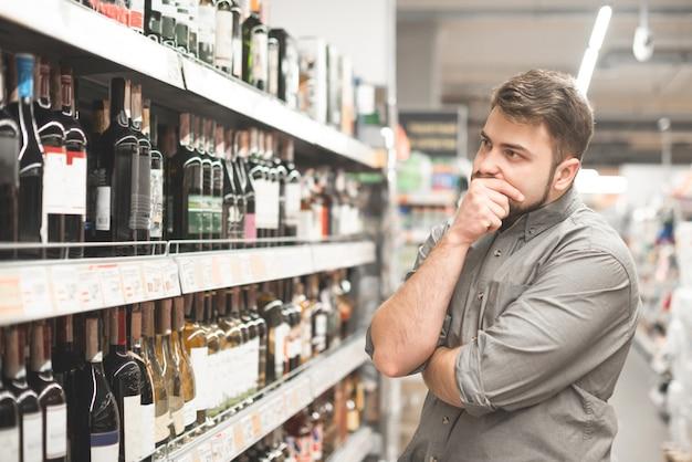 Hombre americano en chaqueta de jeans y boina negra sosteniendo la cesta y mirando una botella de vino, comprando en el supermercado.