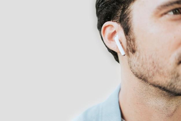Hombre americano escuchando música en auriculares inalámbricos closeup
