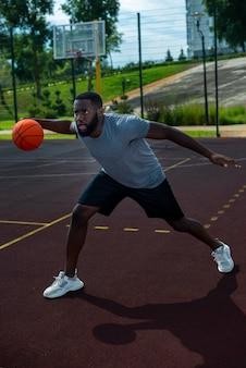 Hombre americano jugando baloncesto tiro largo