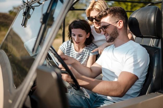 Hombre y amigas comprobando el mapa mientras viaja en coche