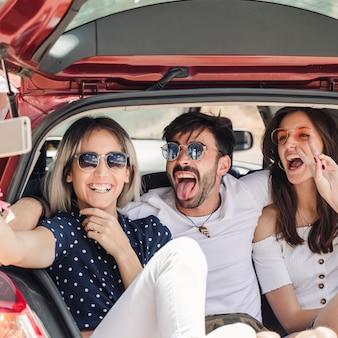 Hombre con amigas sentada en el carro del coche posando para autorretrato