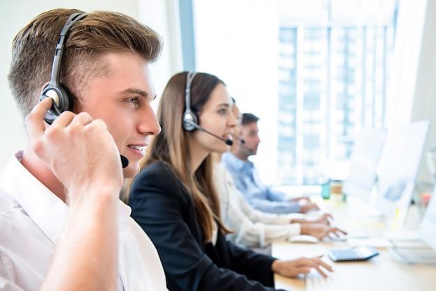 Hombre amistoso sonriente que trabaja en la oficina del centro de atención telefónica con el equipo