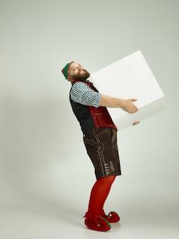 Hombre amistoso vestido como un gnomo divertido posando sobre un gris aislado
