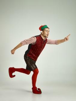 Hombre amistoso vestido como un gnomo divertido posando sobre un gris aislado Foto gratis