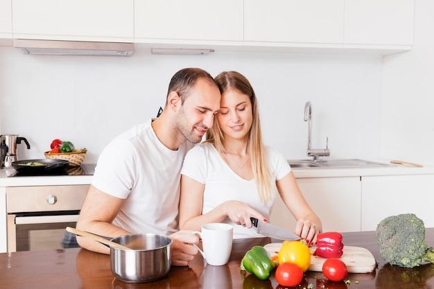 Hombre amoroso sentado con su esposa cortando las verduras con un cuchillo