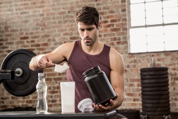 Hombre añadiendo suplemento de estaño a la botella