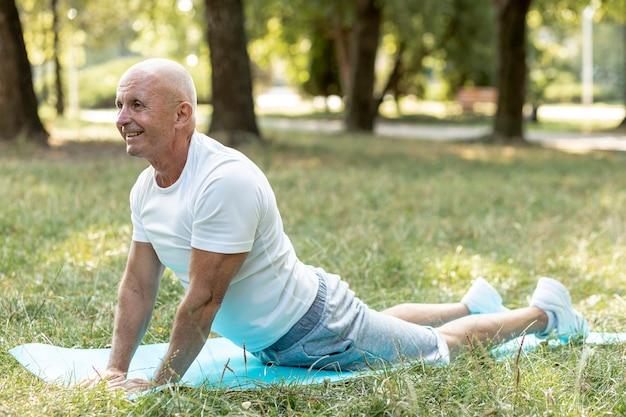 Hombre anciano feliz practicando yoga afuera