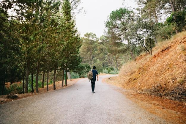 Hombre andando en camino en bosque
