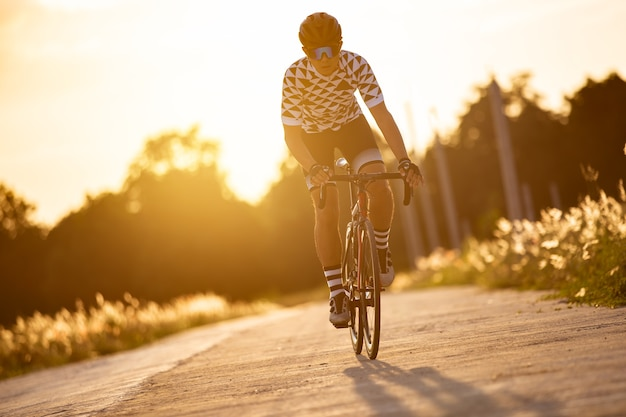 El hombre andar en bicicleta al atardecer la imagen del ciclista en movimiento en el fondo en la noche