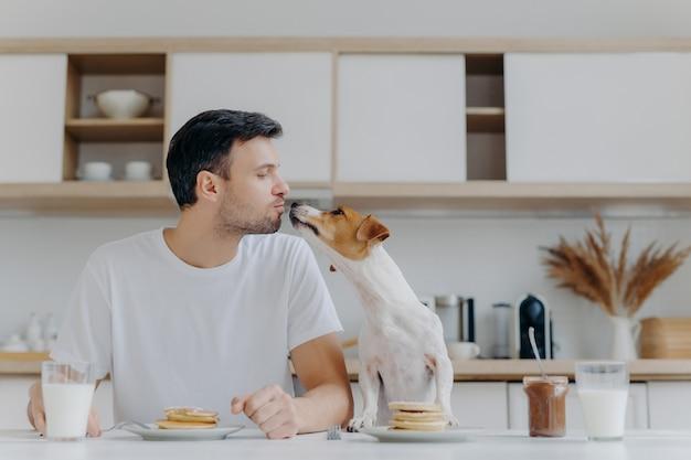 Hombre anfitrión besa con perro, come deliciosos panqueques