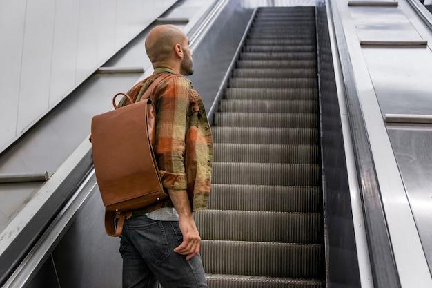 Hombre de ángulo bajo en escalera móvil