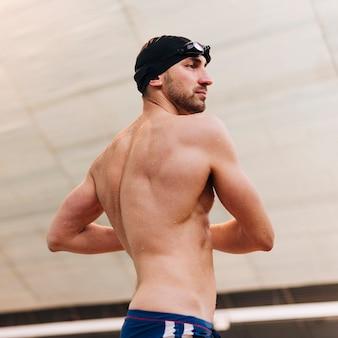 Hombre de ángulo bajo estiramiento antes de nadar
