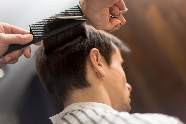 Hombre de ángulo bajo que consigue un corte de pelo
