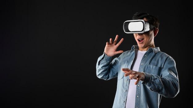 Hombre de ángulo bajo con simulador de realidad virtual