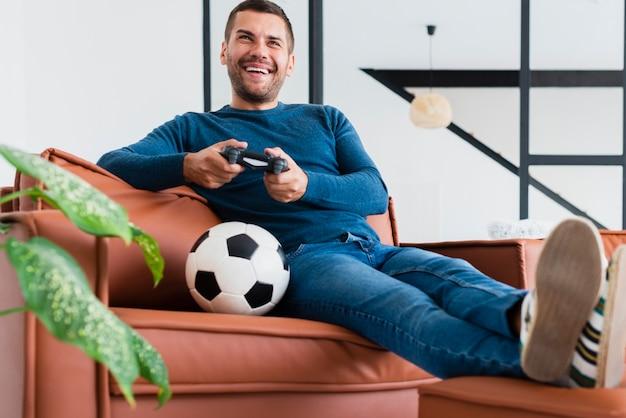 Hombre de ángulo bajo en el sofá jugando juegos