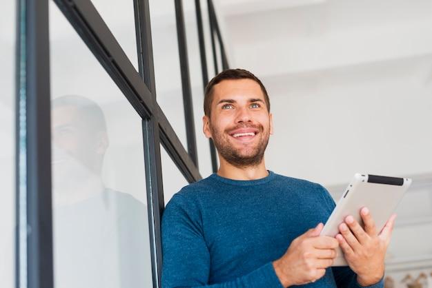 Hombre de ángulo bajo con tableta en casa