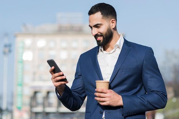 Hombre de ángulo bajo usando móvil