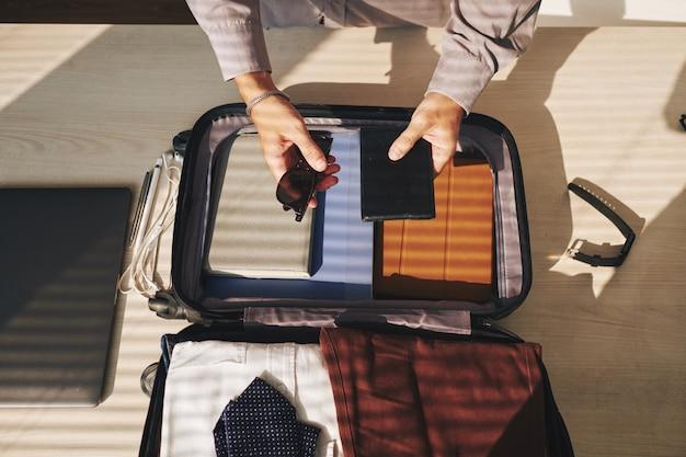Hombre anónimo embalaje maleta para viajar