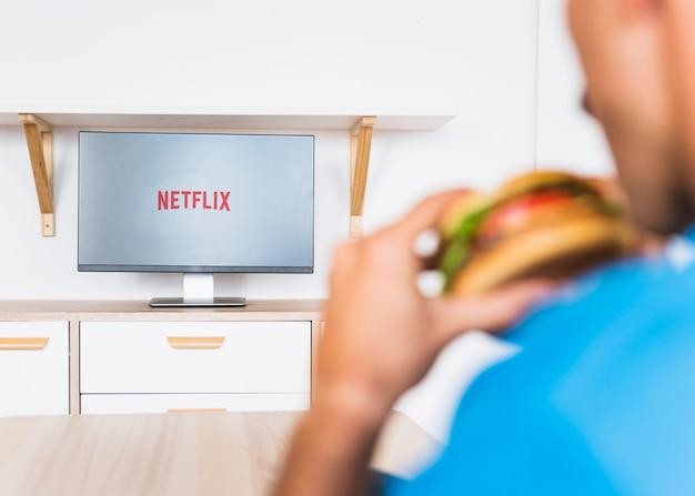 Hombre anónimo con hamburguesa viendo series de televisión