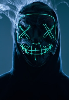 Hombre anónimo ocultando su rostro detrás de la máscara de neón en un humo de color
