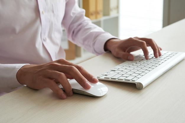 Hombre anónimo recortado que computa en el teclado blanco y que usa el ratón blanco
