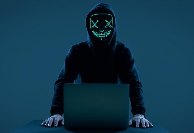 Hombre anónimo con una sudadera con capucha negra y máscara de neón pirateando una computadora