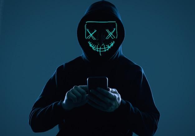 Hombre anónimo con una sudadera con capucha negra y máscara de neón pirateando un teléfono inteligente