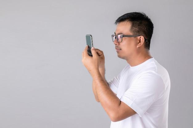 Hombre con anteojos y tratando de mirar el teléfono inteligente