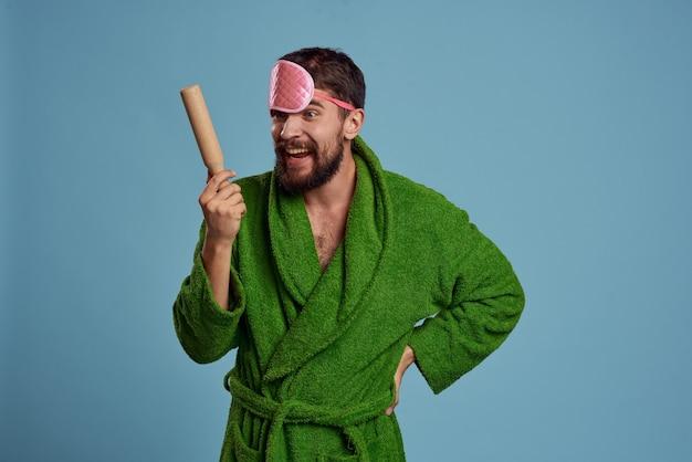 Un hombre con un antifaz rosa para dormir sostiene un rodillo en su mano