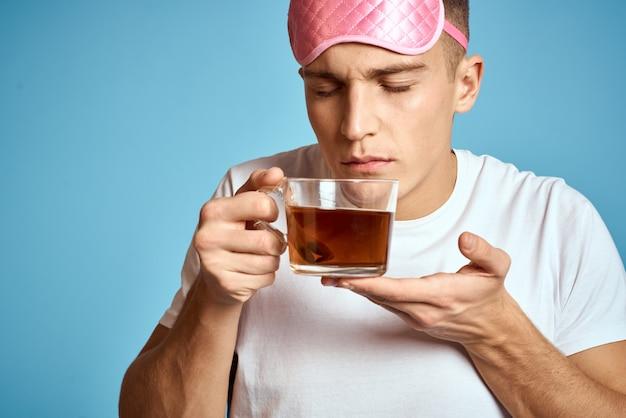 Hombre con antifaz rosa y taza de té
