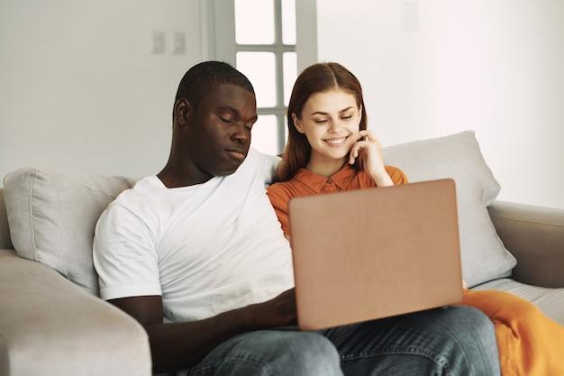Hombre de apariencia africana y mujer con portátil se sientan en el interior del sofá en el interior
