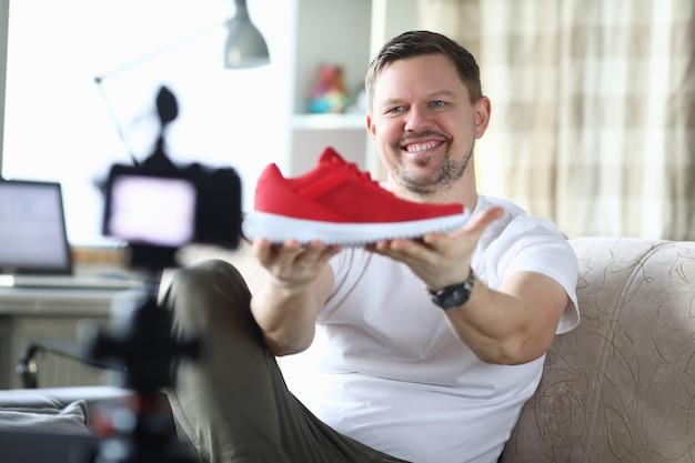 El hombre en un apartamento está filmando la revisión de nuevas zapatillas de deporte