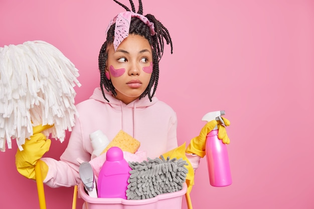 El hombre aplica almohadillas de colágeno debajo de los ojos para reducir las arrugas, posa cerca de la canasta con detergentes y productos de limpieza.