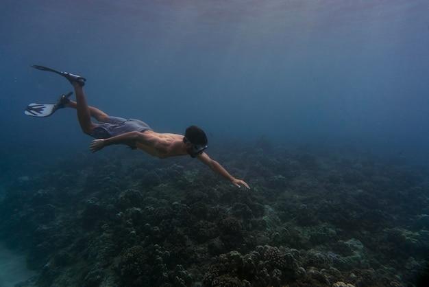 Hombre apnea con aletas bajo el agua