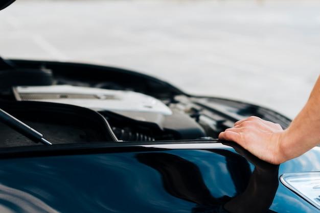 Hombre apoyado en auto con capó abierto