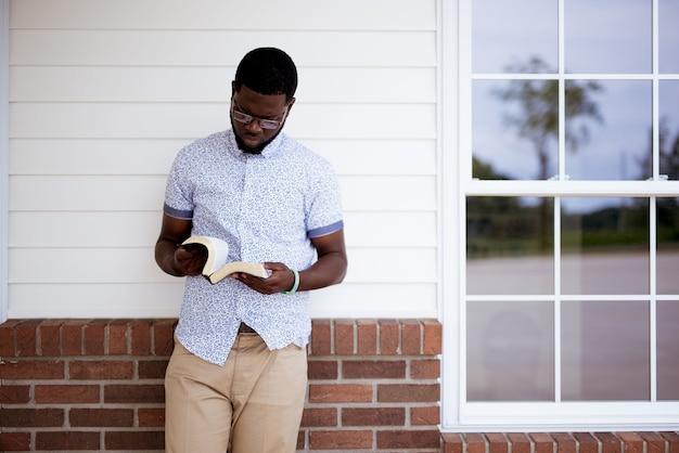 Hombre apoyado contra una pared mientras lee la biblia