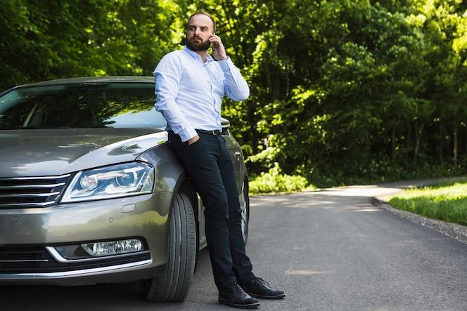 Hombre apoyado en el coche hablando por teléfono inteligente