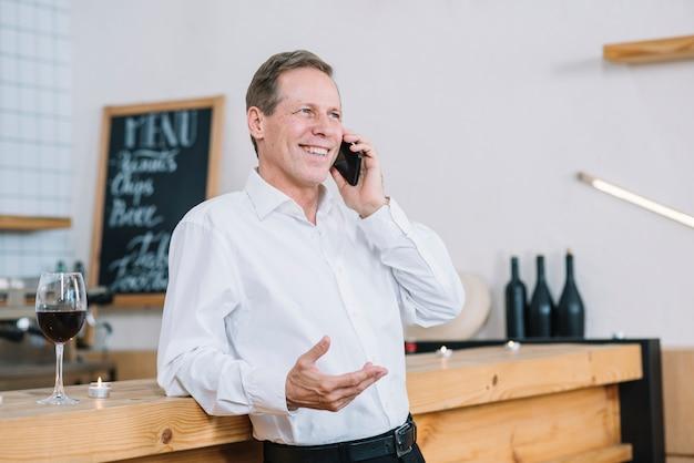 Hombre apoyado en la mesa y hablando por teléfono