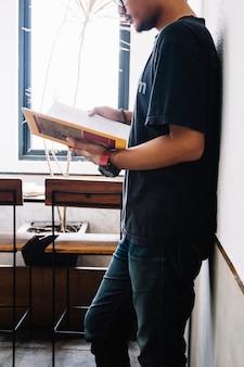Hombre apoyado en la pared y libro de lectura