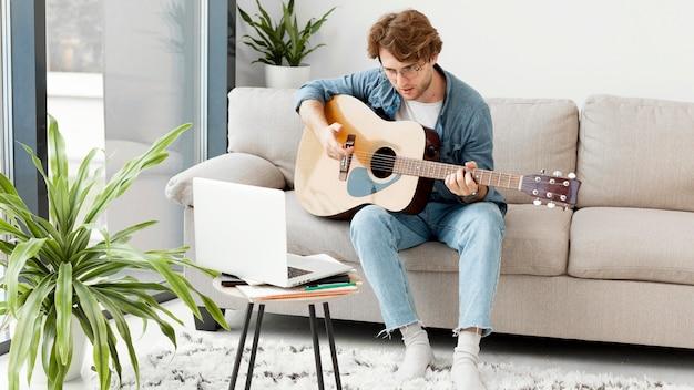 Hombre aprendiendo guitarra en línea y sentado en el sofá