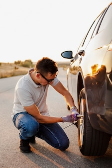 Hombre apretando los tornillos de la rueda del coche